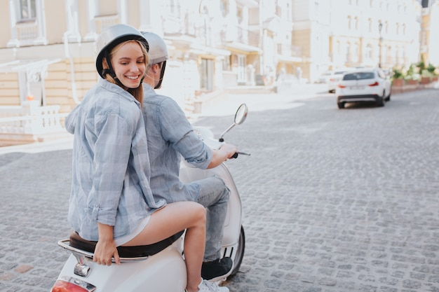 Attractive woman is posing on a motorcycle while his boyfriend drives