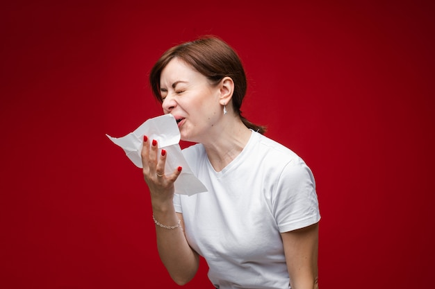 Attractive woman is sick, she coughs and sneezes