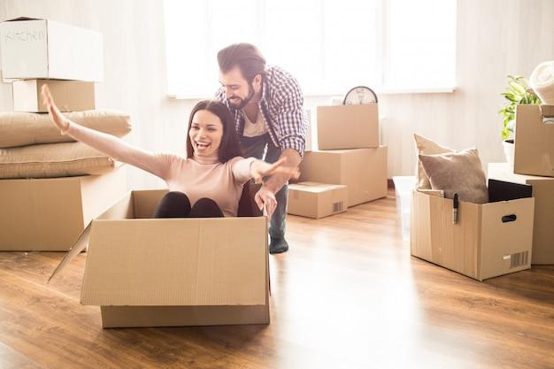 Привлекательная женщина сидит на коробке. ее мужчина толкает ее, чтобы она могла ездить. эти люди выглядят счастливыми и довольными
