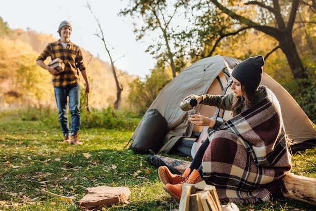 Привлекательная женщина ждет его и пьет чай возле палатки