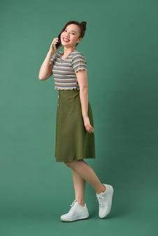 魅力的な女性が携帯電話で歩いて孤立