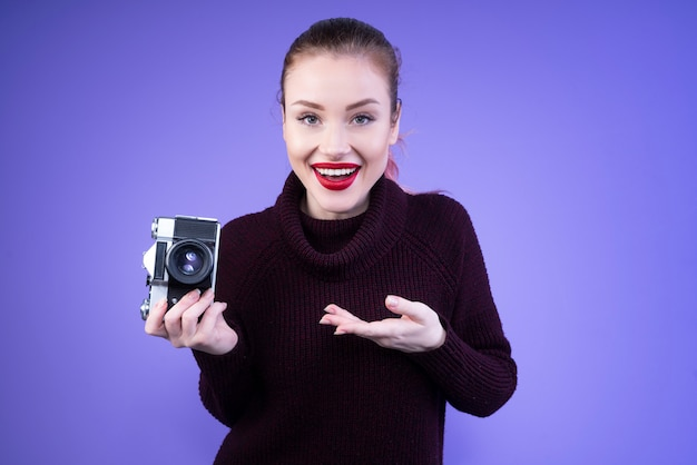 Attractive woman in knitted jumper shows us her new camera