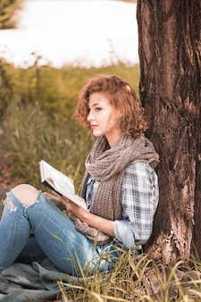 Attractive woman leaning on tree and holding book in park