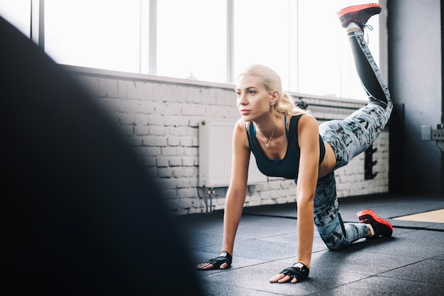 Attractive woman lift leg in gym