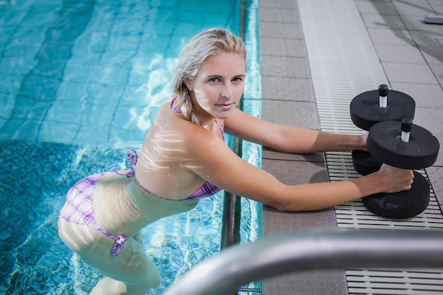 Attractive woman lifting dumbbells in the pool