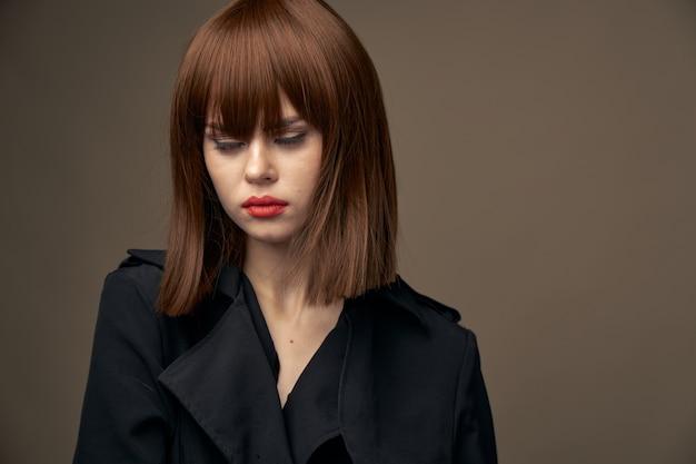魅力的な女性の明るい肌の黒いコートベージュの背景