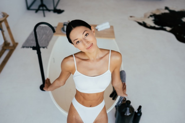 Donna attraente in lingerie in posa vicino al bagno. ragazza in posa per la fotocamera