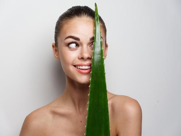 魅力的な女性は彼女の目の前に緑の葉を見て、明るい背景のコピースペースに微笑む