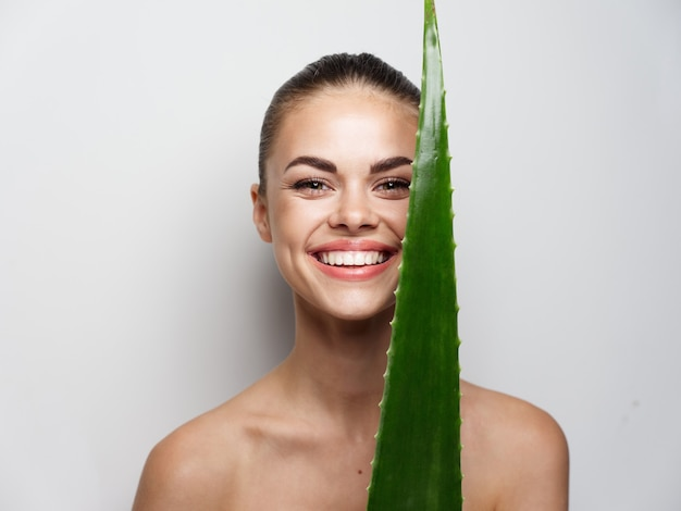 Attractive woman looks at a green leaf before her eyes and smiles on a light background