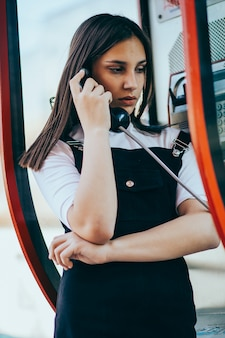 An attractive woman making a public telephone call from a phone booth