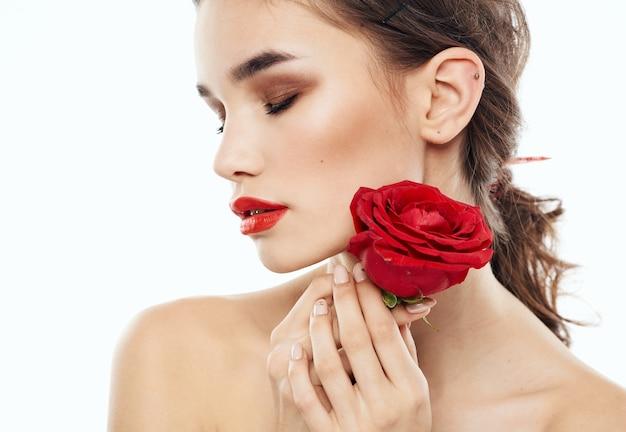 むき出しの肩と花の感情の魅力を持つ魅力的な女性モデル。