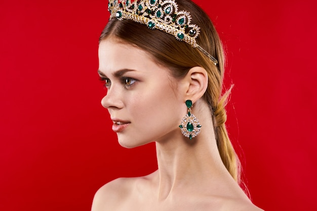 Attractive woman naked shoulders crown decoration red background