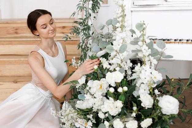 피아노와 꽃 근처 매력적인 여자