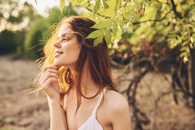 夏のポーズをとる魅力的な木の枝の近くの魅力的な女性