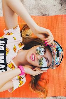 アクセサリーキャップサングラスを身に着けている夏の熱帯の休暇でスタイリッシュなカラフルな衣装でヘッドフォンで音楽を聴いて、上からヨガマットビューに横たわって幸せに笑ってビーチで魅力的な女性