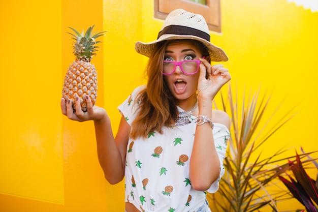 裸足で座っている麦わら帽子を着て感情的に笑って変な表情で夏休みの魅力的な女性は驚いた