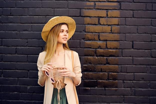 帽子と眼鏡の黒いレンガの壁を身に着けている通りの魅力的な女性。高品質の写真