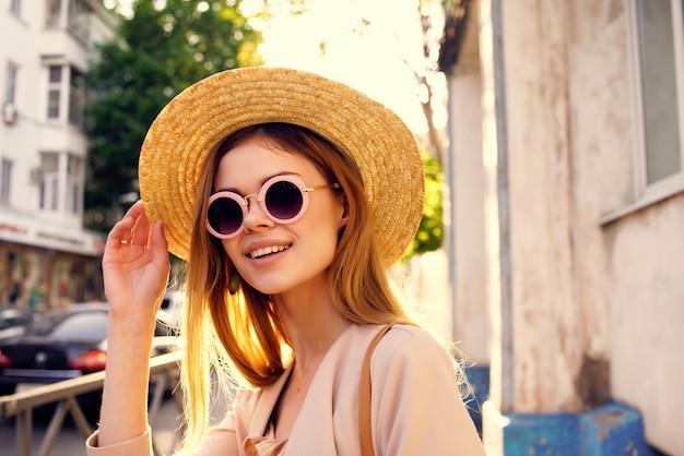 帽子とメガネのライフスタイルを身に着けている通りの魅力的な女性