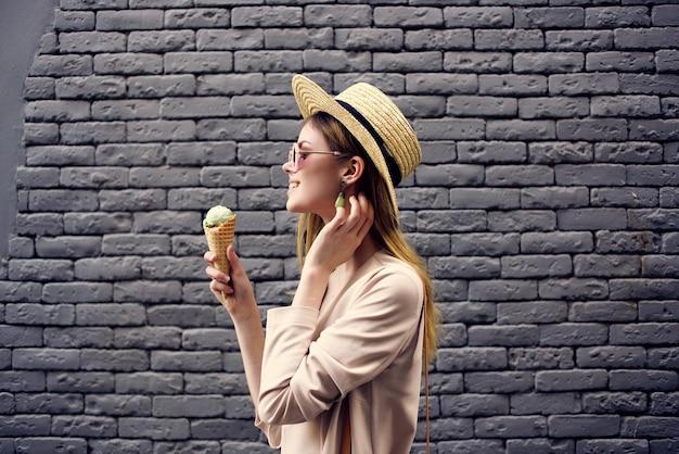 アイスクリームの休暇の楽しみを持つ通りの魅力的な女性