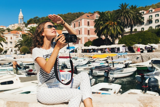 カメラで写真を撮るクルーズで海沿いのヨーロッパで休暇中の魅力的な女性