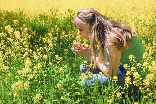 Привлекательная женщина на желтом цветочном саде.
