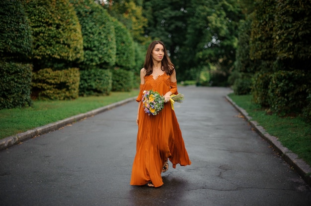 Attractive woman in orange dress walking on the road with bouquet of flowers