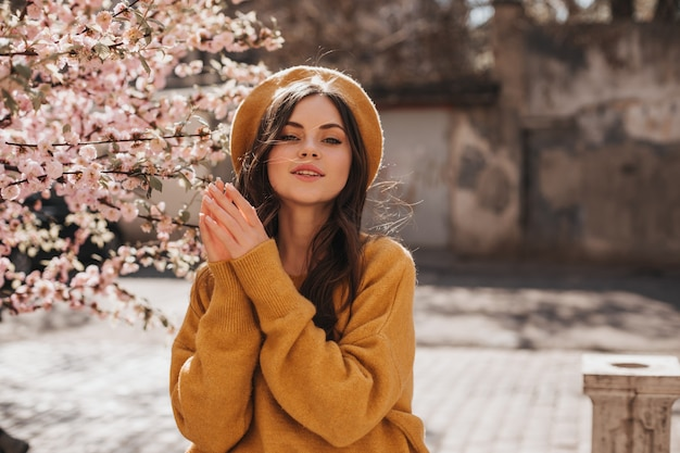 Attractive woman in orange sweater and beret poses beside sakura. dark-haired curly lady in hat walking in sunny spring city
