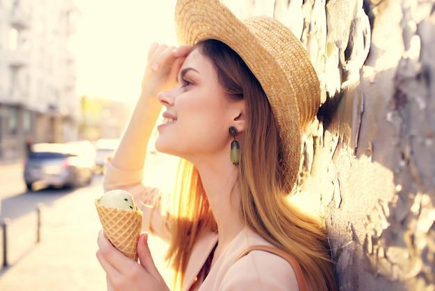 魅力的な女性の屋外散歩はアイスクリーム散歩旅行モデルを食べる