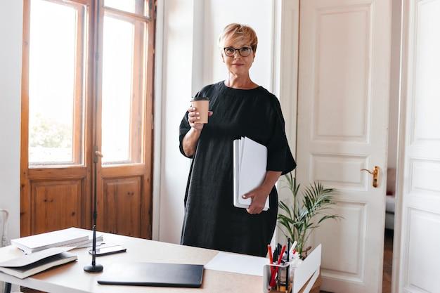 Attraente donna in abito oversize pone con una tazza di tè