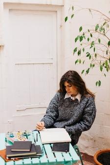 Attractive woman painting in sketchbook