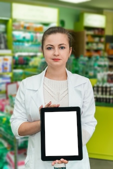 Attractive woman pharmacist showing tablet screen in drugstore