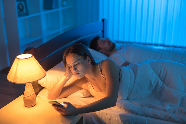 The attractive woman phone in the bed. night time