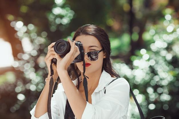 야외 공원에서 dslr 카메라로 이미지를 찍는 매력적인 여자 사진 작가. 화려한 행복