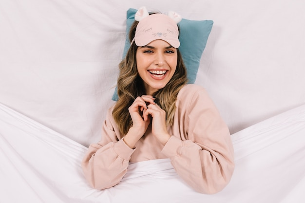 Attractive woman in pink sleep mask posing in bed