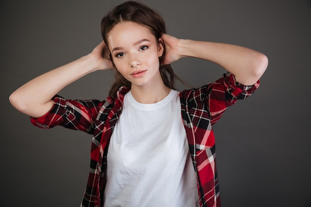 Attractive woman in plaid shirt standing with hands behind head