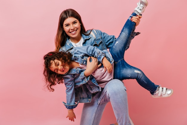 Attractive woman playing with little daughter on pink background. studio shot of mom and preteen kid in denim jackets.