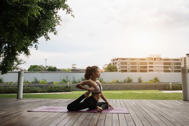 Attractive woman playing yoga for her good health