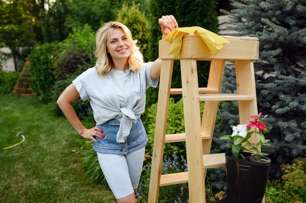 Attractive woman poses at wooden stairs in the garden. female gardener takes care of plants outdoor, gardening hobby, florist lifestyle and leisure
