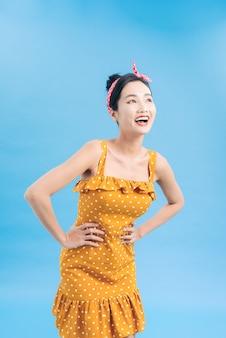 青の上に水玉模様のドレスでポーズをとる魅力的な女性。ピンナップスタイル。