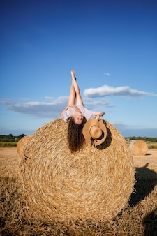 Attractive woman posing in the mown wheat fields with sheaf and sky in the village. hay bales in the field after harvest