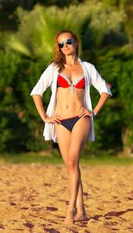 해변에서 포즈를 취하는 매력적인 여자