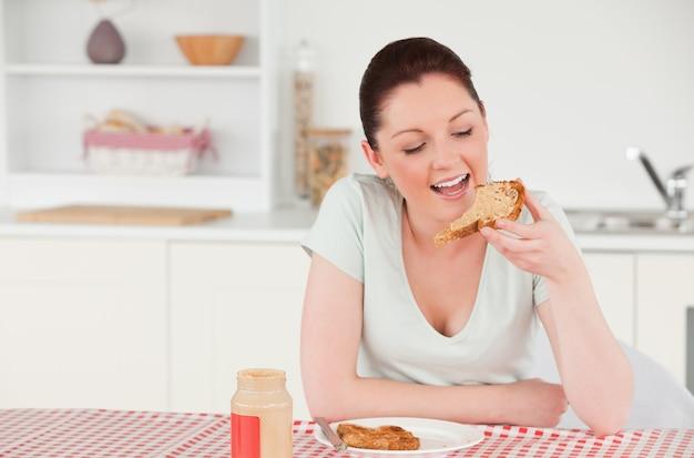 빵 한 조각을 먹는 동안 포즈 매력적인 여자