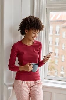 그녀의 집에서 휴대 전화와 함께 포즈를 취하는 매력적인 여자