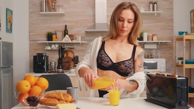 부엌에서 아침 식사를 위해 유리에 신선한 주스를 붓는 매력적인 여자. 문신을 한 젊은 섹시한 매혹적인 금발 여성이 건강하고 천연 수제 오렌지 주스를 마시고 상쾌한 일요일 아침