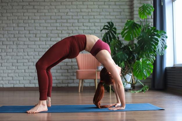 Attractive woman practicing yoga, standing in bridge exercise, urdhva dhanurasana pose, working out, wearing sportswear.