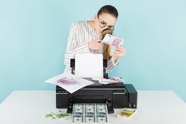 Attractive woman prints cash with magnifying glass