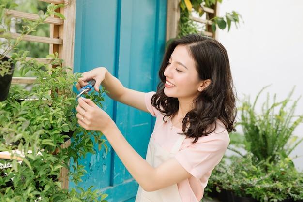 정원에서 secateurs와 나무의 매력적인 여자 가지 치기