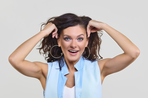 Привлекательная женщина удивленно подняла руки к голове
