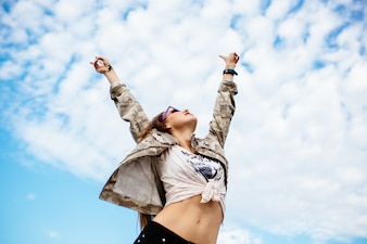 Attractive woman raised her hands up, enjoying perfect day, freedom