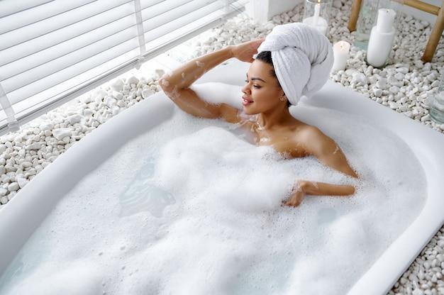 魅力的な女性が泡でお風呂でリラックス。バスタブの女性、スパの美容とヘルスケア、バスルームのウェルネストリートメント、背景の小石とキャンドル